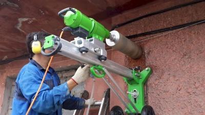 Оператор алмазного бурения выполняет отверстие в кирпичной стене